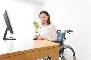 車椅子でデスクワークをする外国人の女性の写真素材 [FYI04712368]