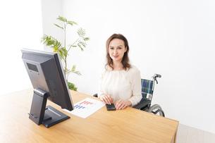 車椅子でデスクワークをする外国人の女性の写真素材 [FYI04712374]