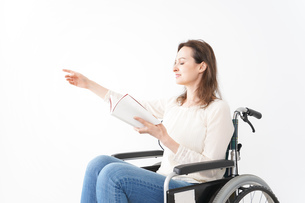 車椅子に乗り読書をする外国人の女性の写真素材 [FYI04712377]