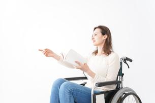 車椅子に乗り読書をする外国人の女性の写真素材 [FYI04712383]