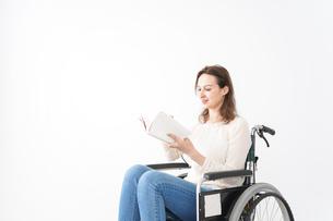 車椅子に乗り読書をする外国人の女性の写真素材 [FYI04712384]