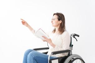 車椅子に乗り読書をする外国人の女性の写真素材 [FYI04712385]
