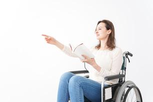 車椅子に乗り読書をする外国人の女性の写真素材 [FYI04712391]
