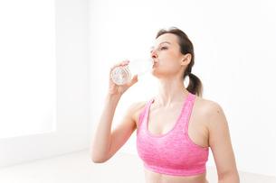 スポーツウェアを着て水分補給をする外国人の女性の写真素材 [FYI04712478]