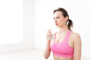スポーツウェアを着て水分補給をする外国人の女性の写真素材 [FYI04712485]