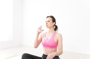 スポーツウェアを着て水分補給をする外国人の女性の写真素材 [FYI04712487]