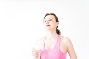 スポーツウェアを着て水分補給をする外国人の女性の写真素材 [FYI04712505]