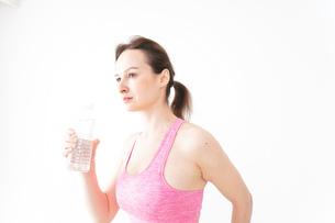 スポーツウェアを着て水分補給をする外国人の女性の写真素材 [FYI04712506]