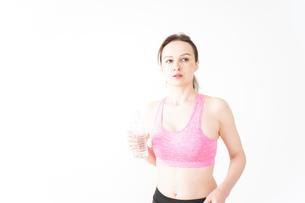 スポーツウェアを着て水分補給をする外国人の女性の写真素材 [FYI04712507]