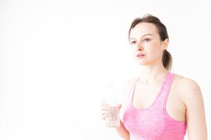 スポーツウェアを着て水分補給をする外国人の女性の写真素材 [FYI04712509]