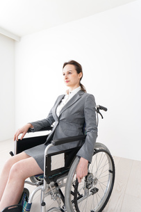 車椅子に乗って仕事をする外国人の女性の写真素材 [FYI04712554]