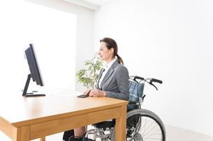 車椅子に乗って仕事をする外国人の女性の写真素材 [FYI04712556]