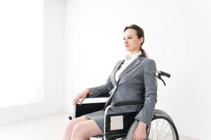 車椅子に乗って仕事をする外国人の女性の写真素材 [FYI04712558]