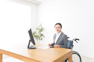 車椅子に乗って仕事をする外国人の女性の写真素材 [FYI04712563]