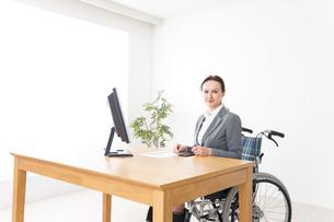 車椅子に乗って仕事をする外国人の女性の写真素材 [FYI04712564]