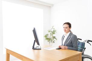 車椅子に乗って仕事をする外国人の女性の写真素材 [FYI04712566]
