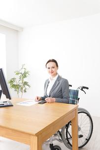 車椅子に乗って仕事をする外国人の女性の写真素材 [FYI04712569]