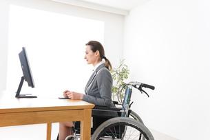 車椅子に乗って仕事をする外国人の女性の写真素材 [FYI04712573]