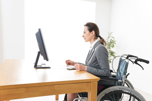 車椅子に乗って仕事をする外国人の女性の写真素材 [FYI04712574]