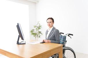 車椅子に乗って仕事をする外国人の女性の写真素材 [FYI04712575]