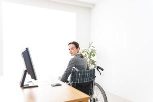 車椅子に乗って仕事をする外国人の女性の写真素材 [FYI04712576]