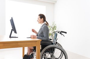 車椅子に乗って仕事をする外国人の女性の写真素材 [FYI04712580]