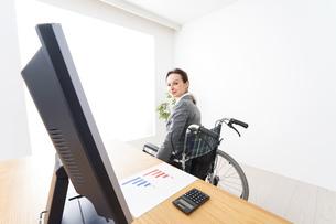 車椅子に乗って仕事をする外国人の女性の写真素材 [FYI04712585]