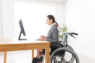 車椅子に乗って仕事をする外国人の女性の写真素材 [FYI04712586]