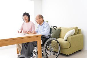 契約をする高齢の夫婦の写真素材 [FYI04712724]