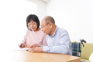 契約をする高齢の夫婦の写真素材 [FYI04712747]