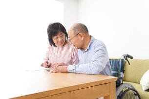 契約をする高齢の夫婦の写真素材 [FYI04712748]