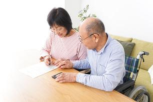 契約をする高齢の夫婦の写真素材 [FYI04712750]