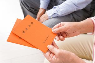 年金手帳を持つ高齢の夫婦の写真素材 [FYI04712848]