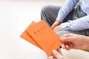 年金手帳を持つ高齢の夫婦の写真素材 [FYI04712857]