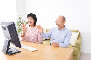 パソコンでテレビ電話をする高齢の夫婦の写真素材 [FYI04712977]