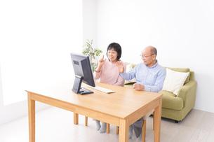 パソコンでテレビ電話をする高齢の夫婦の写真素材 [FYI04712978]
