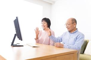 パソコンでテレビ電話をする高齢の夫婦の写真素材 [FYI04712987]