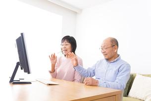 パソコンでテレビ電話をする高齢の夫婦の写真素材 [FYI04712988]