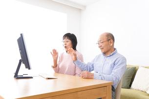 パソコンでテレビ電話をする高齢の夫婦の写真素材 [FYI04712989]