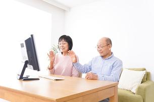 パソコンでテレビ電話をする高齢の夫婦の写真素材 [FYI04712991]