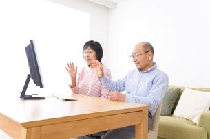 パソコンでテレビ電話をする高齢の夫婦の写真素材 [FYI04712992]