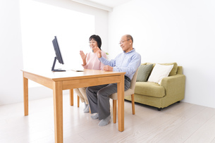 パソコンでテレビ電話をする高齢の夫婦の写真素材 [FYI04712994]