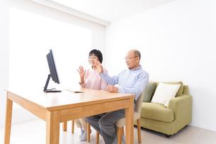 パソコンでテレビ電話をする高齢の夫婦の写真素材 [FYI04712996]