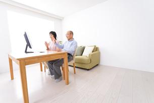 パソコンでテレビ電話をする高齢の夫婦の写真素材 [FYI04712997]