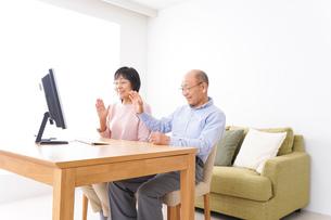 パソコンでテレビ電話をする高齢の夫婦の写真素材 [FYI04712998]