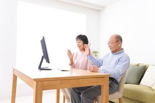 パソコンでテレビ電話をする高齢の夫婦の写真素材 [FYI04712999]