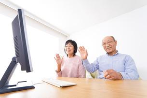 パソコンでテレビ電話をする高齢の夫婦の写真素材 [FYI04713000]
