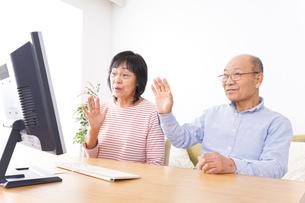 パソコンでテレビ電話をする高齢の夫婦の写真素材 [FYI04713003]