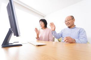 パソコンでテレビ電話をする高齢の夫婦の写真素材 [FYI04713005]