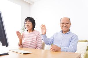 パソコンでテレビ電話をする高齢の夫婦の写真素材 [FYI04713006]